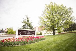 Eastern Kentucky University sign at campus entrance with tree