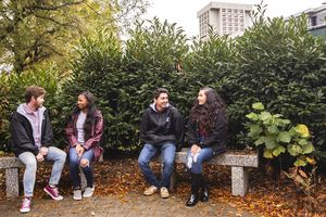 Fours students sitting on benches talking