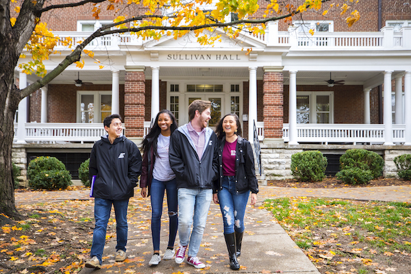 four students walking down sidewalk in a fall scene with building in background