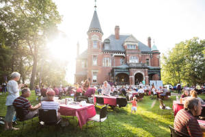 alumni sitting at tables on lawn before historic house