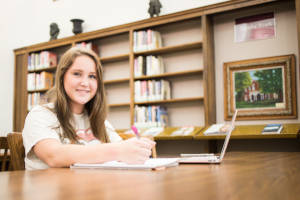 student seated in library
