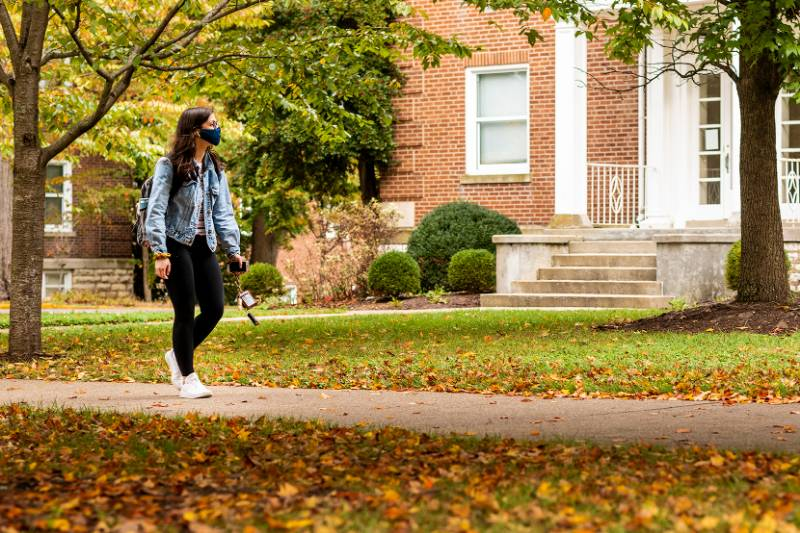 Student walking in front of Palmer building through trees with leaves on ground