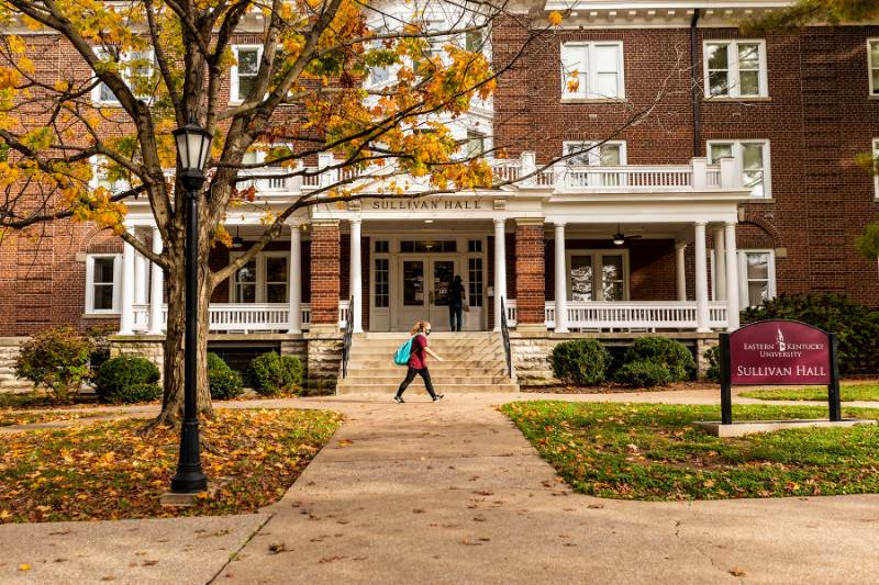 Photo of Sullivan while a student walks by it with orange leaves on the ground.