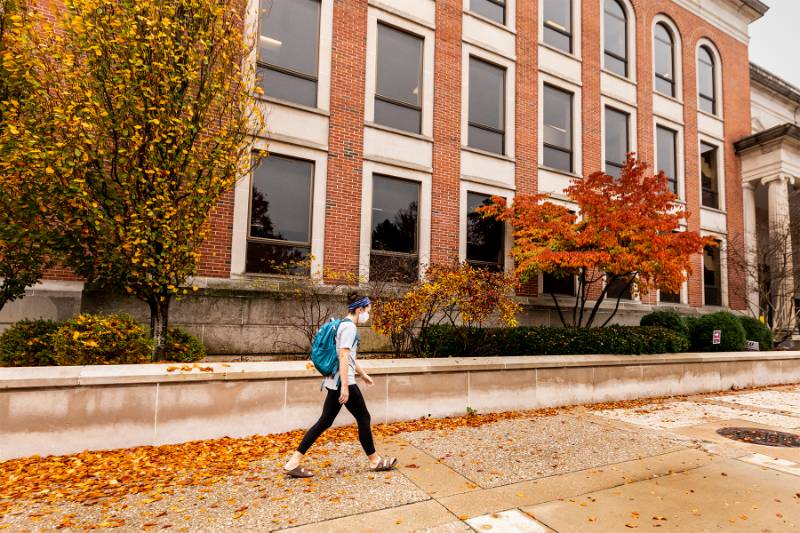 Student walking along side of the library towards  sides entrance. Orange leaves