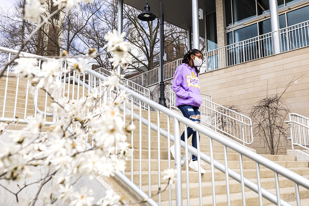Student walking downstairs next to Case Dining Hall. Trees in bloom next to stairs.
