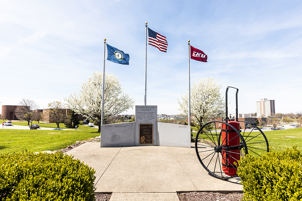 Flags waving in the air above fire and safety memorial. Perkins, Business and technology, and Keen Hall in background.
