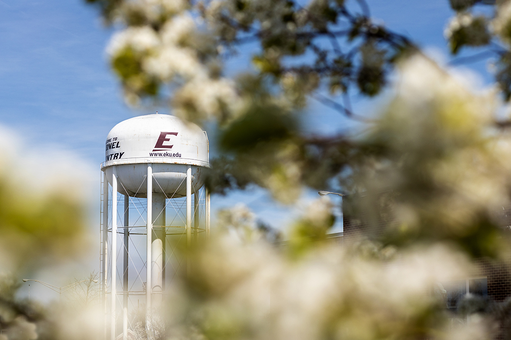 Eastern Kentucky University water tower with power E logo peaking through tree branches.